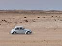 a vw beetle, driving through the desert. 2007-09-02, Sony F828.
