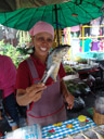 a saleswoman presents fried fish at the food market