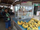 this woman sells fresh bananas and fresh donuts. the ideal shop!