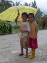 two indonesian boys in the rain.